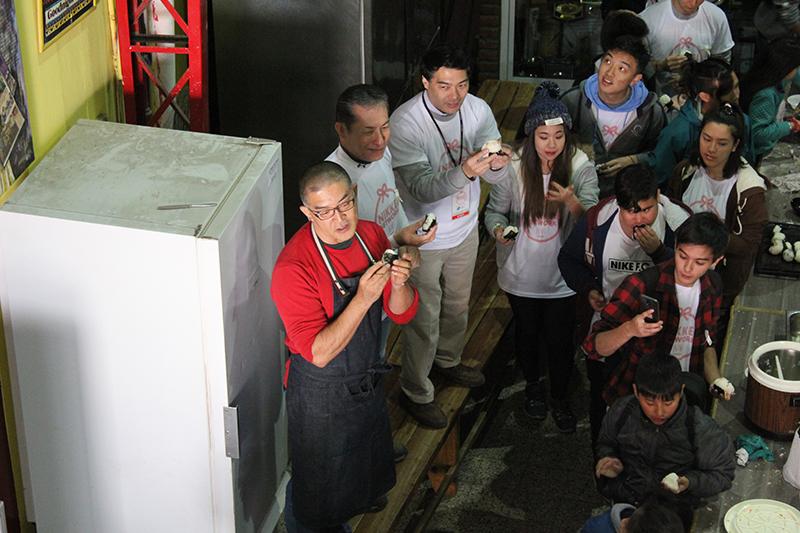 Durante el almuerzo, el chef Takehiro Ohno preparó unos onigiris junto a los jóvenes Nikkei y los niños del lugar. Foto: Japón Hoy