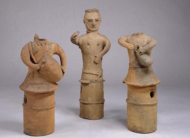 """Izq.: """"Haniwa: Hombre que toca taiko"""" (Sawa – Prefectura Gunma). Haniwa masculino con un tambor.  Centro: Haniwa femenino que baila con un instrumento de percusión que lleva en su mano. Der.: Haniwa con tambor. (Piezas pertenecientes al Museo Nacional de Tokyo)"""